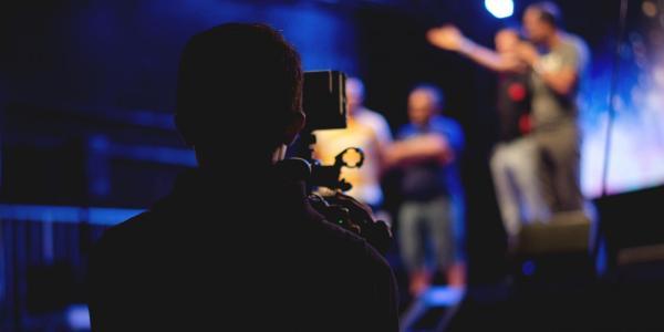 Filmmaker video taping people in a studio
