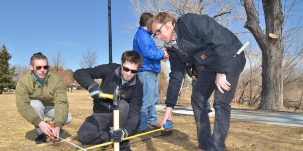 Engineers measuring and installing a stake in the ground.