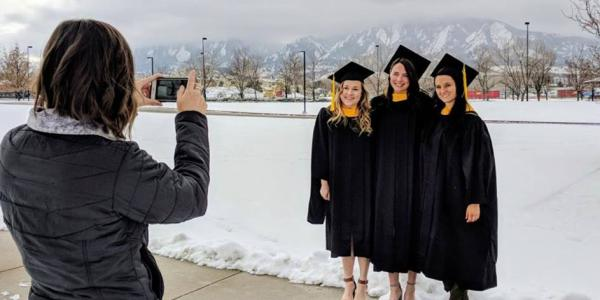 Woman taking picture of graduates