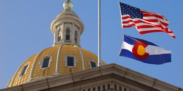 Colorado State Capitol with CO and US flags.