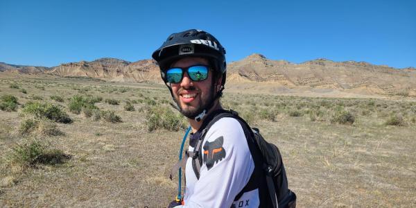 Nicholas Kellaris on a mountain bike with helmet and sunglasses in the desert