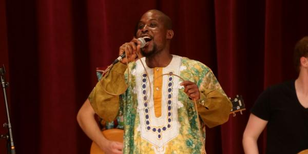 african ensemble director on stage