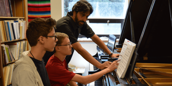 piano teacher working with young students