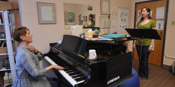 student singing with teacher in studio