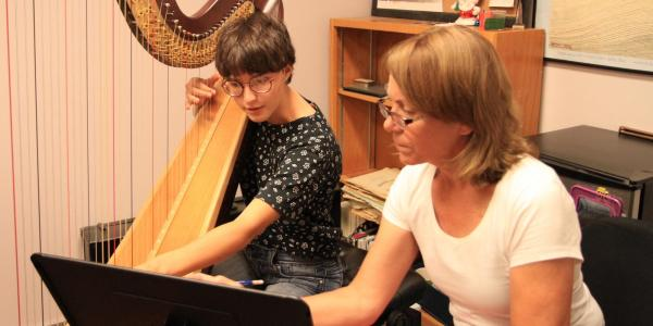 harp student getting a lesson from teacher