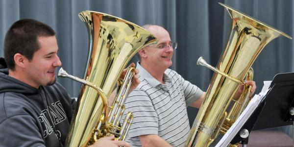 student and faculty member playing tuba