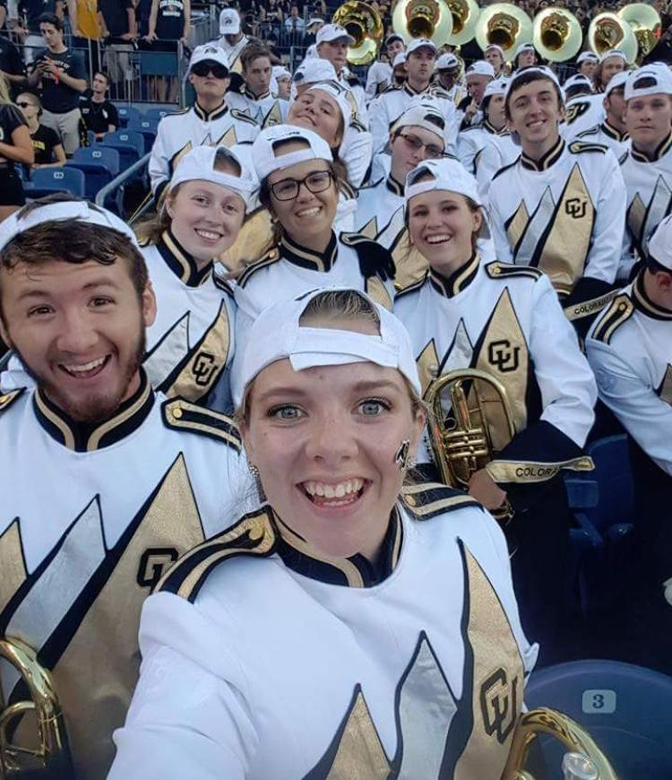 students in marching band uniforms in the stands