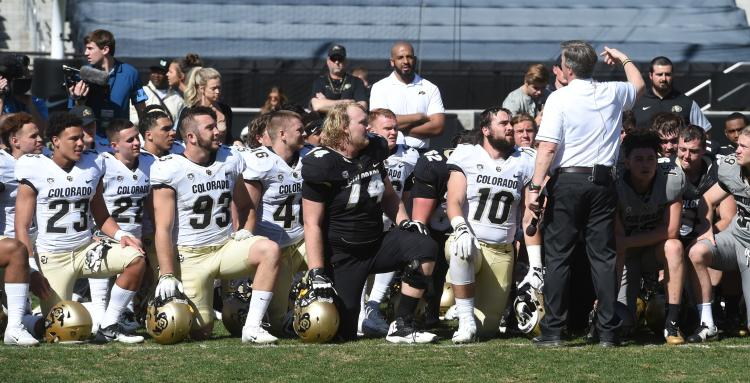 group of football players in a huddle
