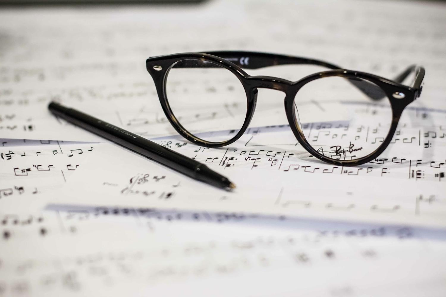 sheet music on desk with pen and glasses on top