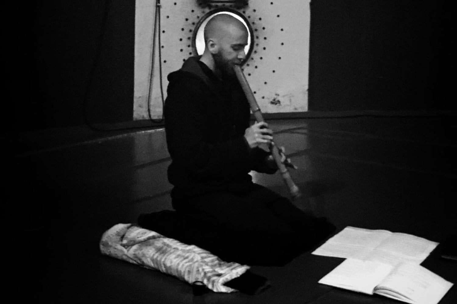 student playing flute on floor