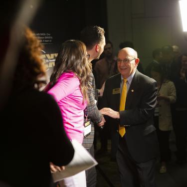 Chancellor Phillip Distefano shaking hands with Baker Machado