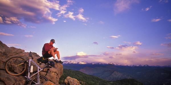 Man sitting on a mountain with laptop