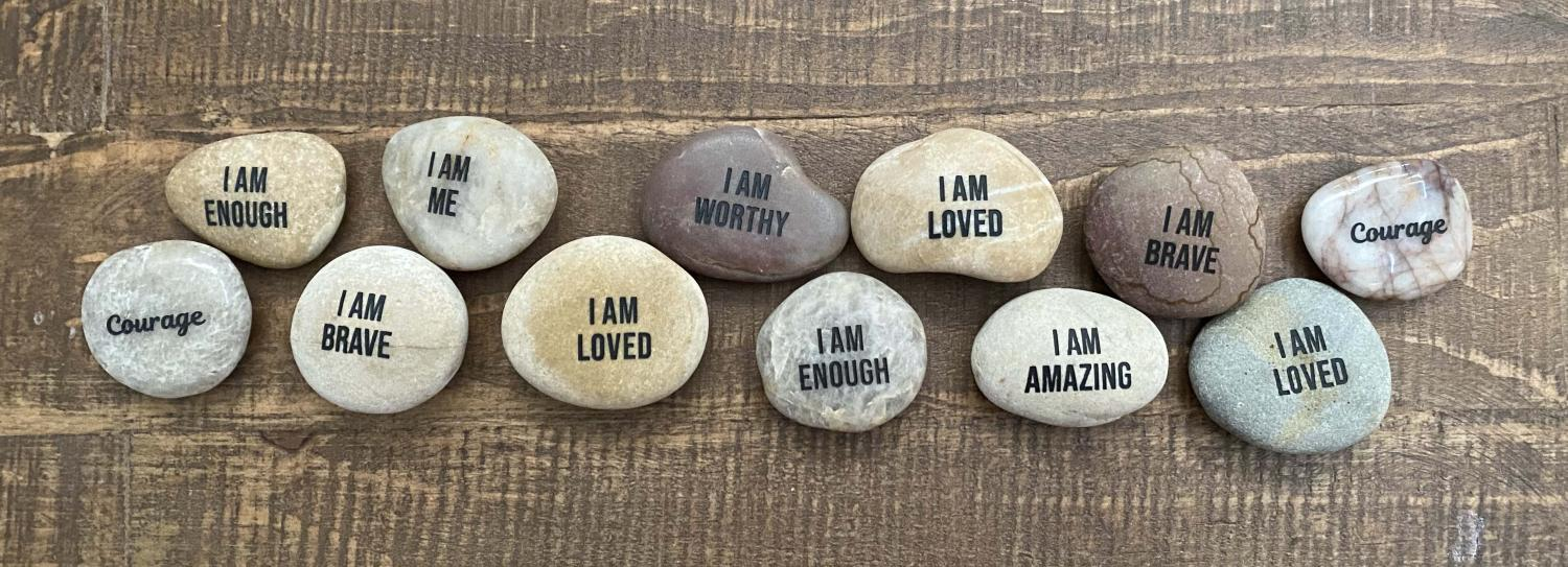 """Stones on a wooden table. The stones have writing on them like, """"I am enough"""", """"I am brave"""", """"I am loved"""", """"I am worthy""""."""