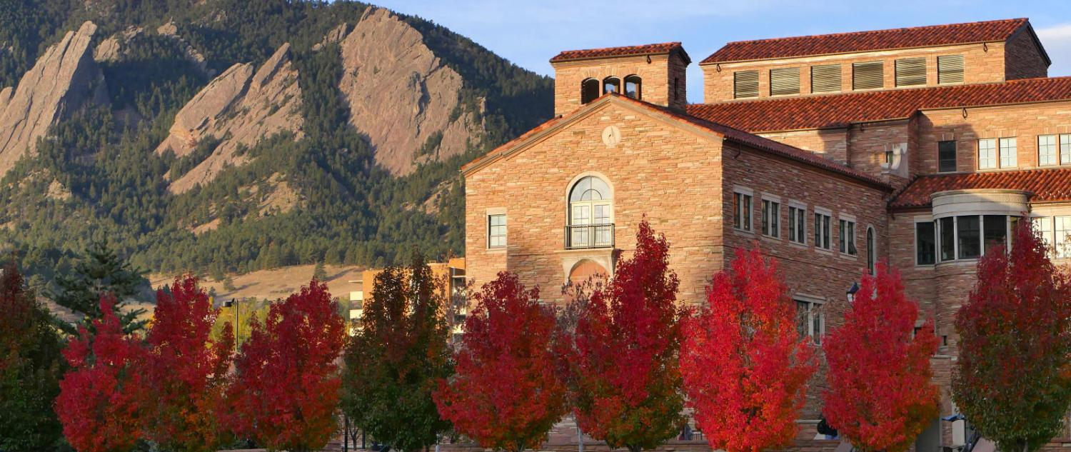 Red fall trees with campus building and flatirons in the back