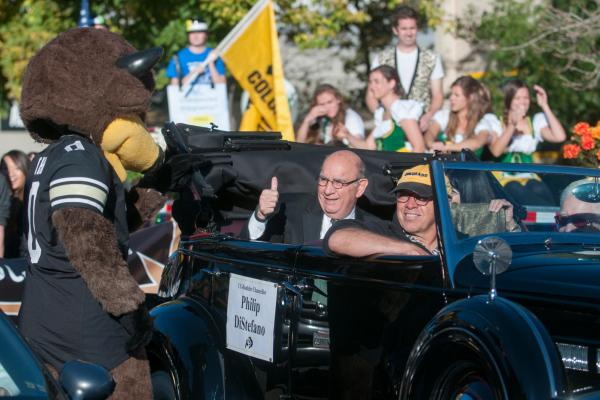 The Chancellor riding in a car during a homecoming parade.
