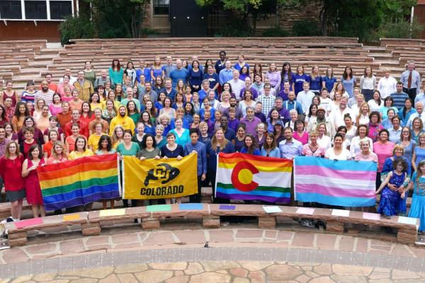 A crowd of CU Boulder members stand in colored shirts in order of the rainbow holding LGBTQIA+ flags