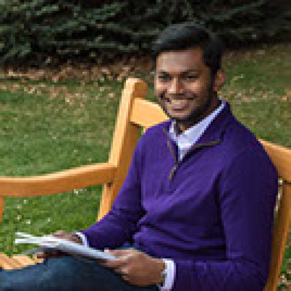 Male student sitting on a bench reading