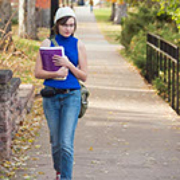 Female student walking on campus path with books