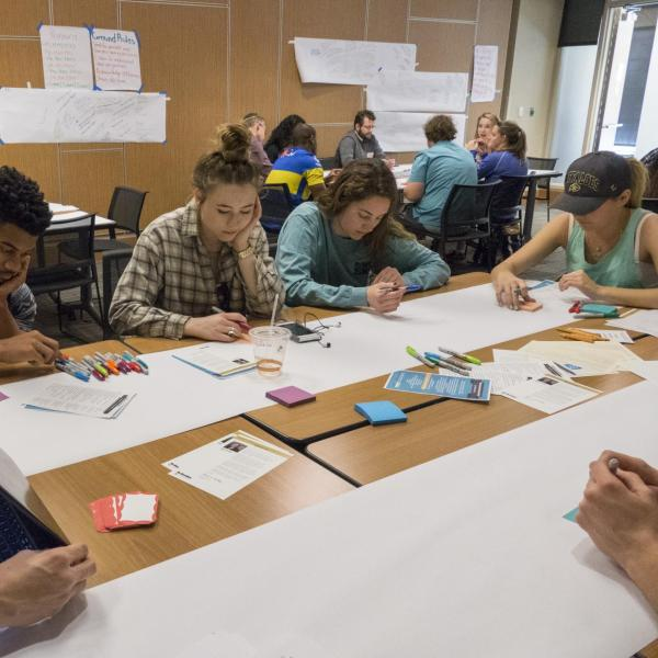 Students around a table working on a banner for a particular summit session