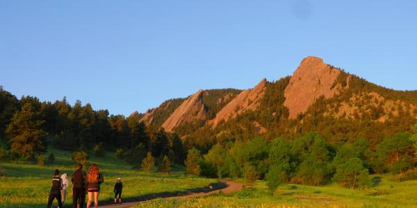 Sunrise over the flatirons as people hike the Chautauqua trail.