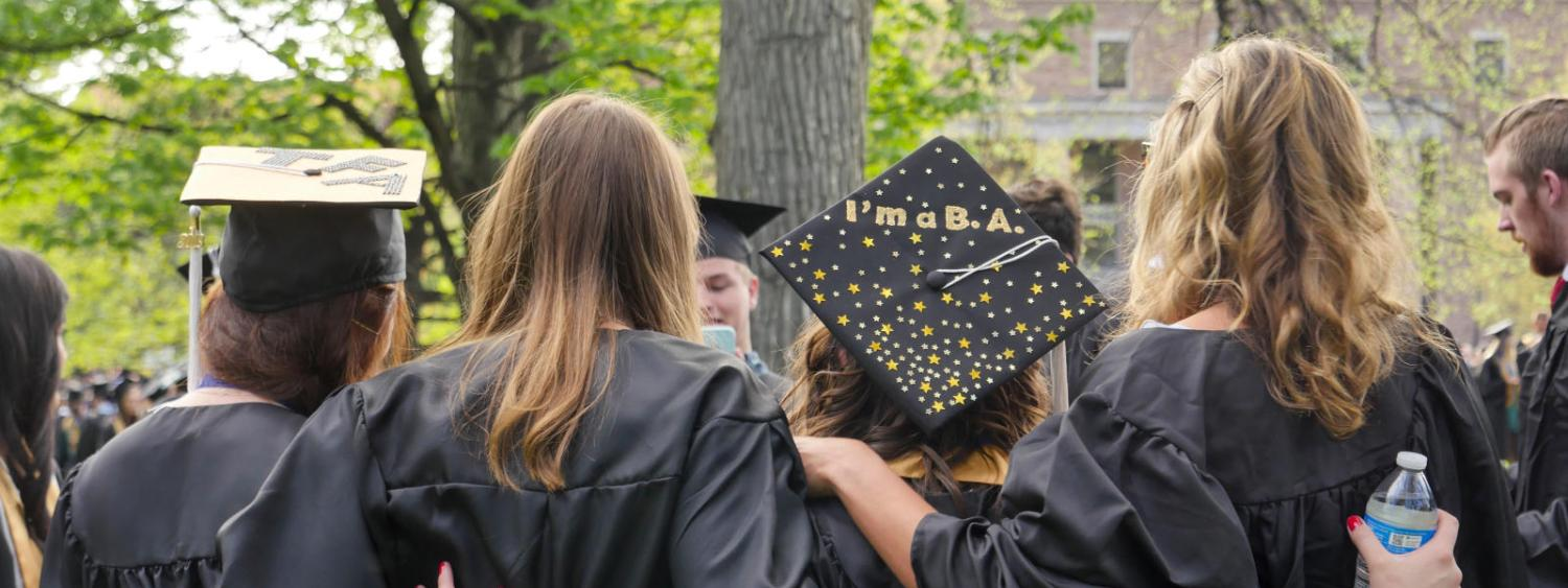 Students standing in a line in their caps and gowns facing away from the camera