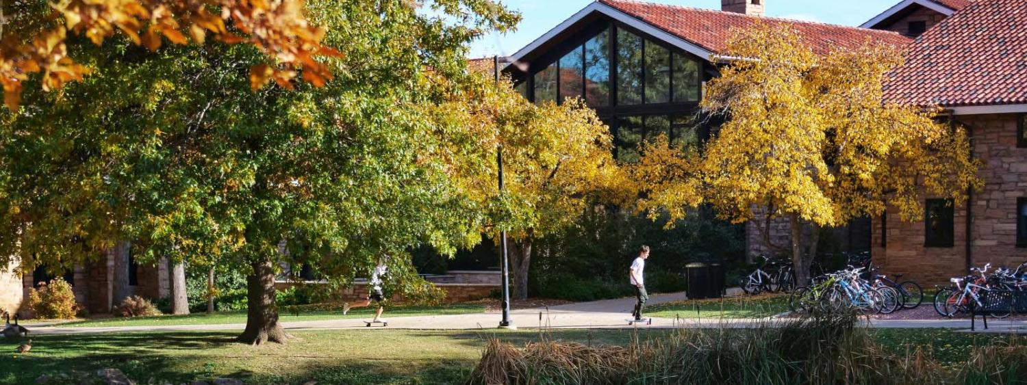 campus building with pond in front fall colors