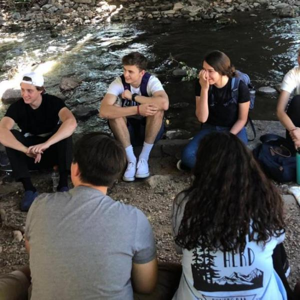 First year seminar students sitting by Boulder Creek during a lesson