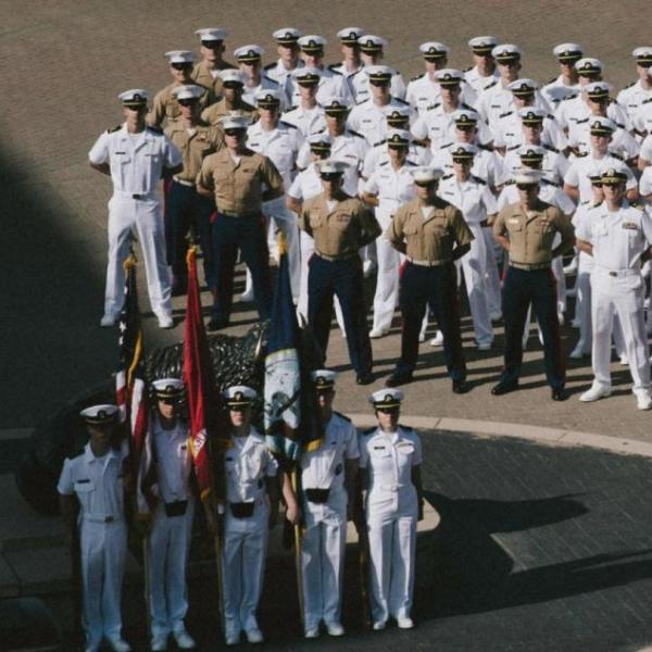 Naval ROTC cadets standing at attention at a flag