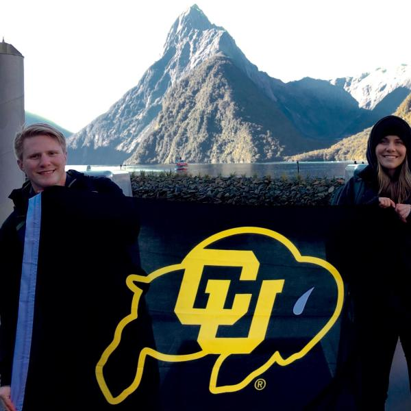 Education abroad students holding up a CU flag in front of a lake in New Zealand
