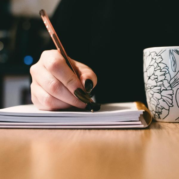 Woman Writing with Be Happy Cup