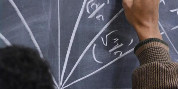 A student doing a math problem on a chalk board