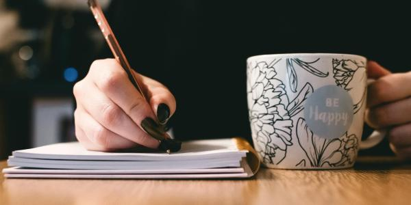 Woman writing with cup