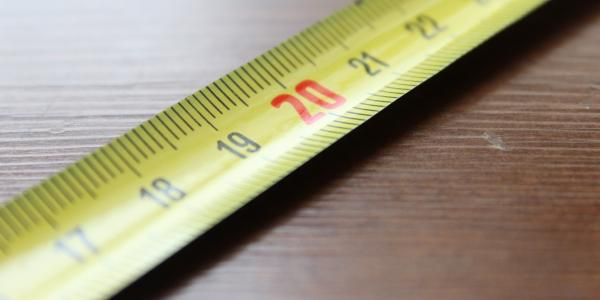 yellow tape measure extended, laying flat on table top