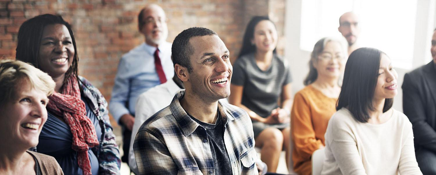 Group of people in a seminar setting sitting down and smiling.