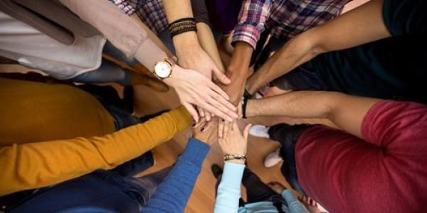 People in a huddle with their hands out laid upon each other.