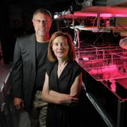 Physics professors Margaret Murnane and Henry Kapteyn of JILA pose next to one of the laser apparatuses in their lab at the University of Colorado Boulder campus.