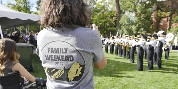 People watch a marching band performance at Family Weekend