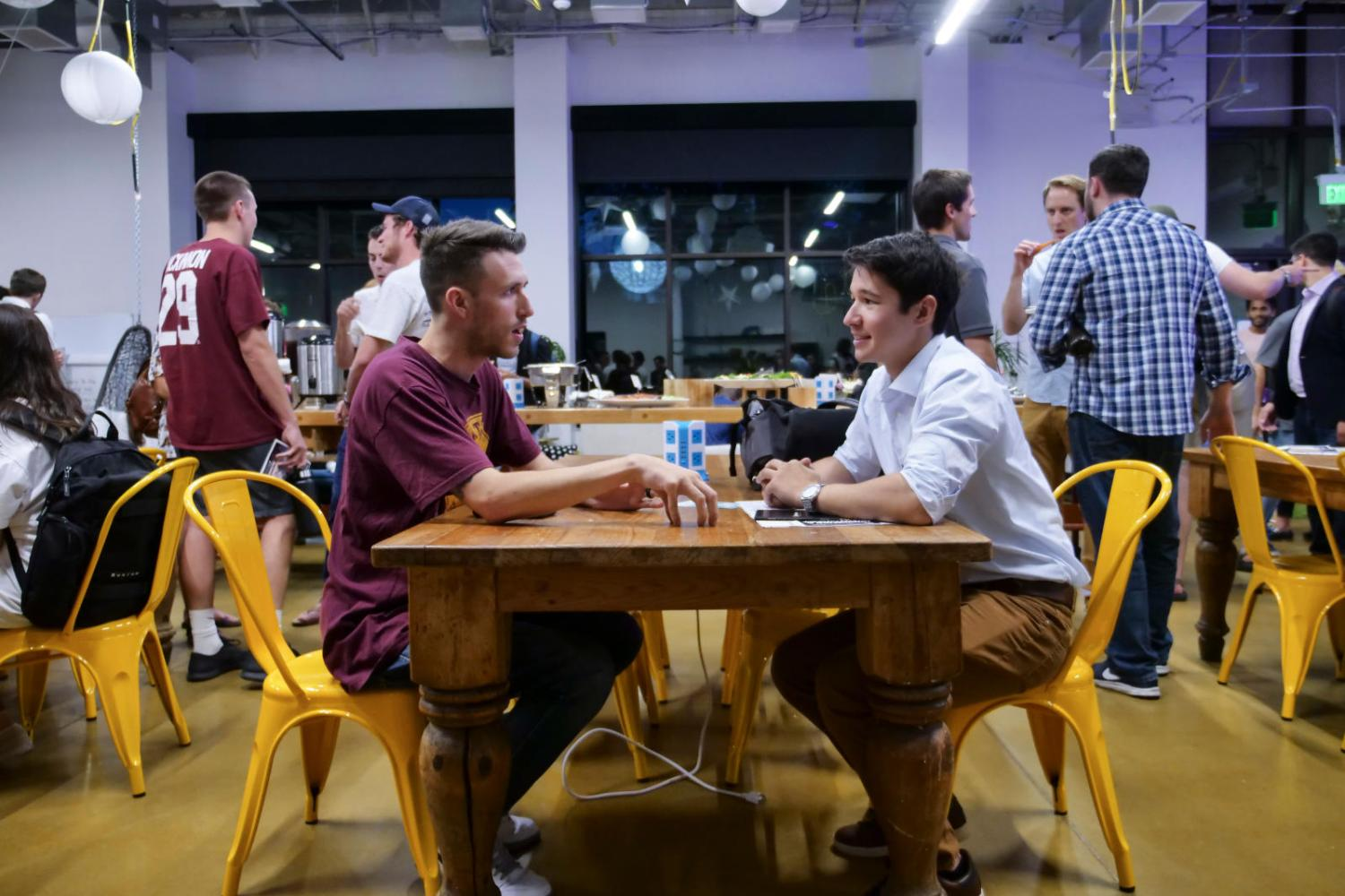 two students have a conversation at a table