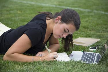Student studying on Farrand Field