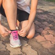 female tying a running shoe