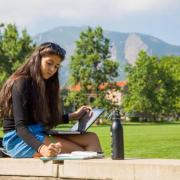 female student studying on farrand field
