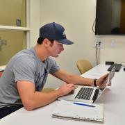 A student works on a laptop in the Business Library at CU Boulder.