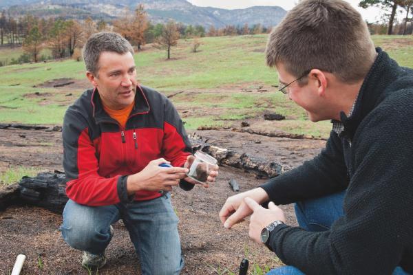 Joe Ryan discusses soil sample with student