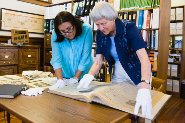 Marjorie McIntosh and colleague look at Latino history materials.