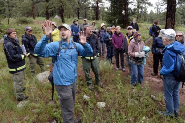 Chris Wanner, a forest ecologist for Boulder's Open Space and Mountain Parks, talks about controlled burns in the area of the south fork of the Shanahan Trial with a group of about 30 people.
