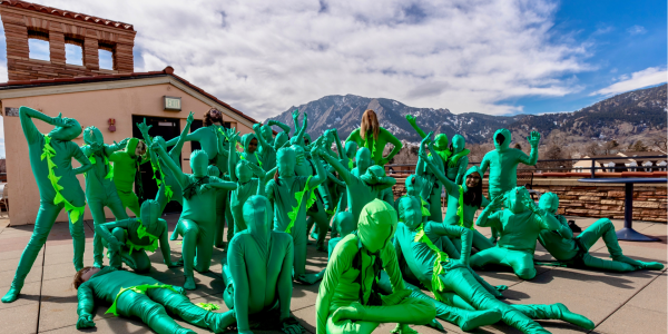 A group of people in green body suits