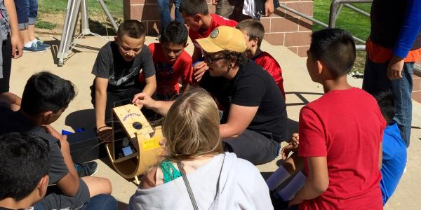CU Boulder astronomy student Sam Strabala searches for sunspots with middle schoolers in Keenesburg as part of a science outreach program.