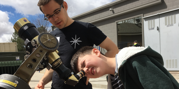 Greeley student looking through a telescope