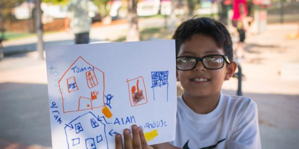 Student showing picture of houses that he drew as part of Growing Up Boulder program