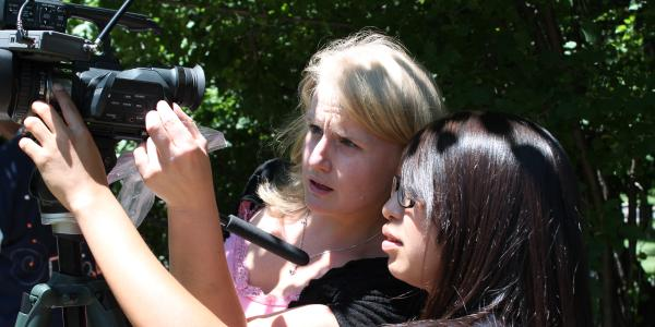 Student and professor looking through a video camera